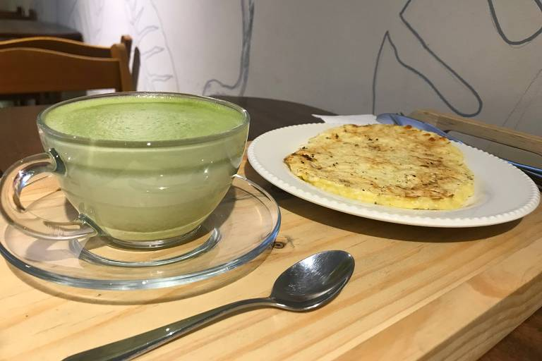 Na Colibri, o pão de queijo é feito na hora em uma chapa e é servido assim, achatadinho; na foto, o salgado está acompanhado de um matchá latte