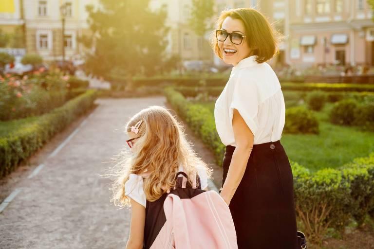 Mãe caminha com a filha até a escola