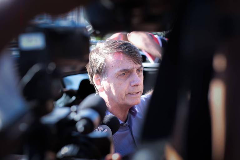 Escoltado por policiais, o presidente eleito, Jair Bolsonaro (PSL), fala com a imprensa na porta do condomínio onde mora, no Rio de Janeiro