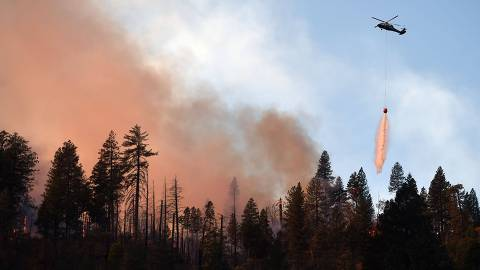 A helicopter drops water on a burning ridge in the Feather River Canyon, east of Paradise, California on November 11, 2018. - The number of dead in a wildfire raging in California rose to 29 on November 11, matching the deadliest in the state's history as recovery teams found six more bodies in the grim search through the wreckage. (Photo by Josh Edelson / AFP)