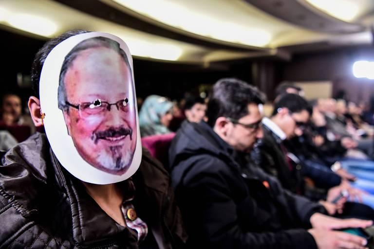 Homem com máscara está na ponta de uma fila de outras pessoas sentadas