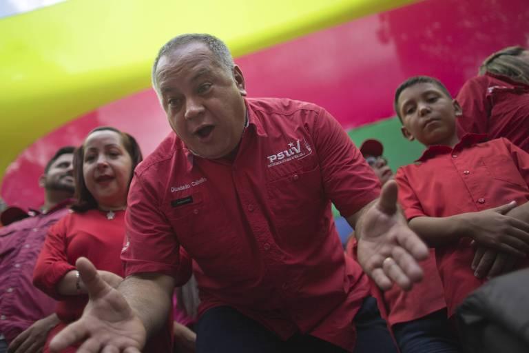 Cabello abre as mãos colocando suas palmas para cima enquanto fala ao lado de militantes sob uma bandeira gigante da Venezuela