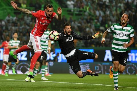 Benfica's Greek forward Konstantinos Mitroglou (L) vies with Sporting's goalkeeper Rui Patricio (C) during the Portuguese league football match Sporting CP vs SL Benfica at the Jose Alvalade stadium in Lisbon on April 22, 2017. / AFP PHOTO / FRANCISCO LEONG ORG XMIT: 2350