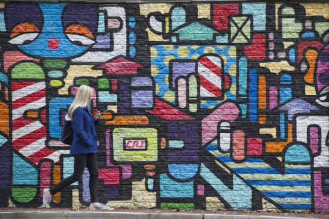A woman walks on a Crystal City sidewalk, in Arlington, Va., is seen Tuesday, Nov. 13, 2018. Amazon has confirmed that it will split its much-anticipated second headquarters between New York City and Arlington, Va. (AP Photo/Cliff Owen) ORG XMIT: VACO106