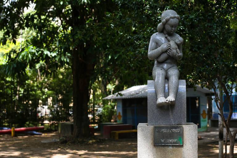 Estátua de criança ninando uma boneca