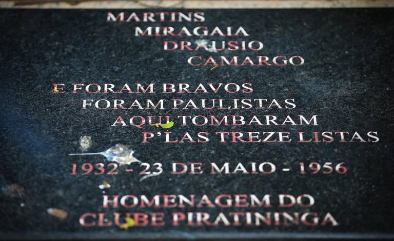 """Placa com os dizeres """"Martins, Miragaia, Drausio e Camargo. Foram bravos, foram paulistas, aqui tombaram pelas treze listas; 1932 - 23 de maio - 1956; homenagem do clube Piratininga"""""""