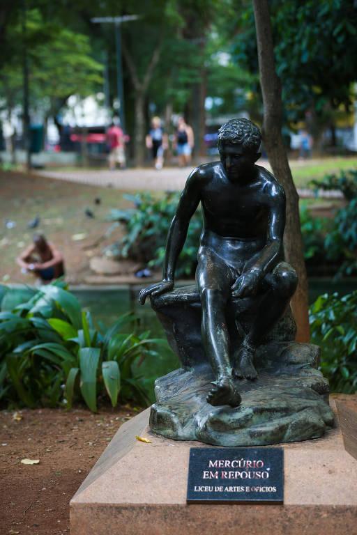 Estátua do deus romano Mercúrio, sentado, com um lago ao fundo