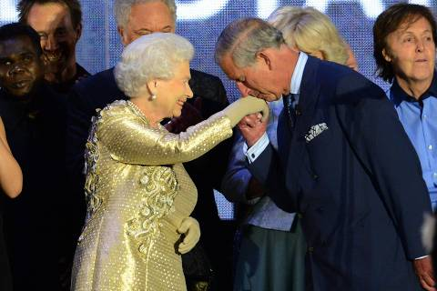 (FILES) In this file photo taken on June 04, 2012 Prince Charles kisses the hand of Britain's Queen Elizabeth II on stage as well as British singer Paul McCartney (R) looks on after the Jubilee concert at Buckingham Palace in London, on June 4, 2012. - Britain's Prince Charles turns 70 on November 14, 2018 as busy as ever, having spent a lifetime forging his own path during his record wait for the throne. (Photo by LEON NEAL / AFP) ORG XMIT: 248