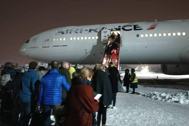 Passageiros embarcam no aeroporto de Irkutsk, na Sibéria, onde ficaram retidos por três dias após problemas em voo da Air France de Paris a Xangai