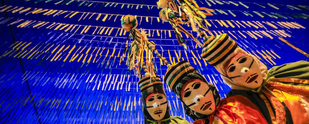Três festeiros usam máscaras brancas e adereços coloridos na cabeça durante desfile em São Caetano de Odivelas