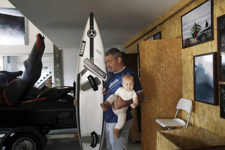 Garret McNamara. surfista nascido no Havaí, segura sua filha e uma prancha de surfe na sua oficina em Nazaré