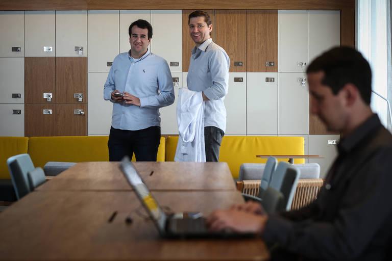 Claudio Mifano e Fabio Soccol em pé atrás de uma pessoa onde trabalha um home com notebook