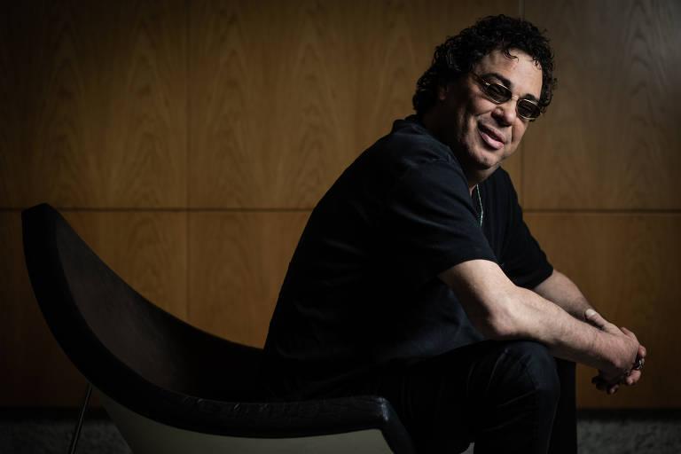 Casagrande está sentado, veste camisa preta, óculos escuros e olha para a câmera