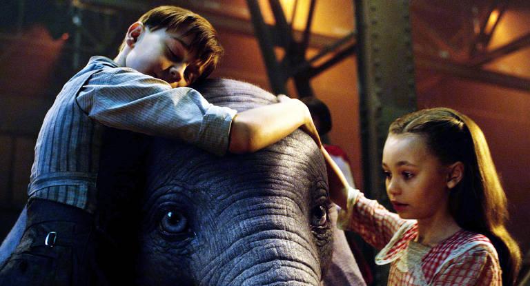 Os personagen Joe (Finley Hobbins) e Milly (Nico Parker) abraçam Dumbo em cena do filme