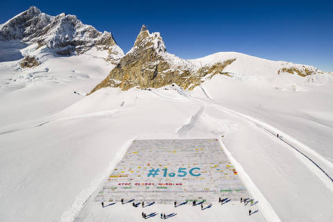 A giant postcard of approximately 2500 square meters made of contributions from over 125'000 individual postcards containing messages aiming to fight climate change and global warming, is pictured on the Aletsch glacier near the Jungfraujoch saddle by the Jungfrau peak, in Switzerland, Friday, November 16, 2018. Each individual postcard includes climate change promises and messages from children and youth originating from 35 countries over the world and aims to establish the Guinness world record of the largest composed postcard with the most overall contributors. The 1.5 degrees Celcius written in the center of the postcard refers to a target of limiting global warming to 1.5°C. (Valentin Flauraud/Keystone via AP) ORG XMIT: DNSC119
