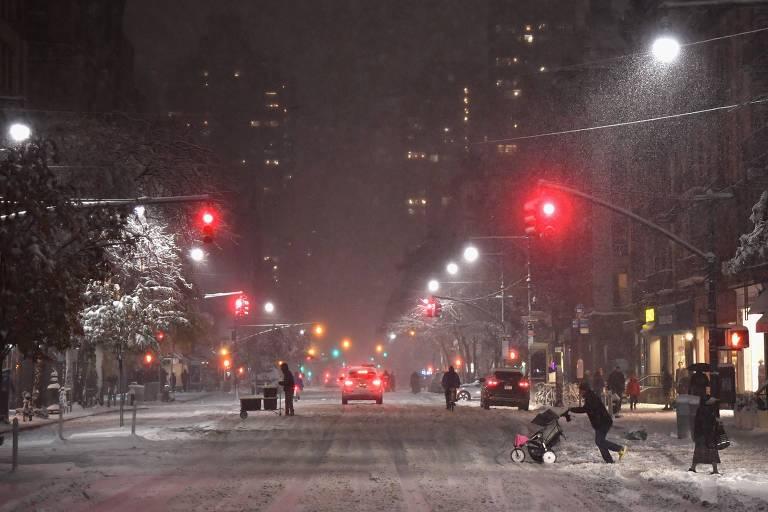 Pedestres em rua durante nevasca na noite de quinta-feira (15) em Nova York