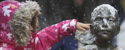 A young girl brushes off snow on the Fearless Girl statue in lower Manhattan on Thursday, Nov. 15, 2018, in New York. (AP Photo/Wong Maye-E) ORG XMIT: NYWM104