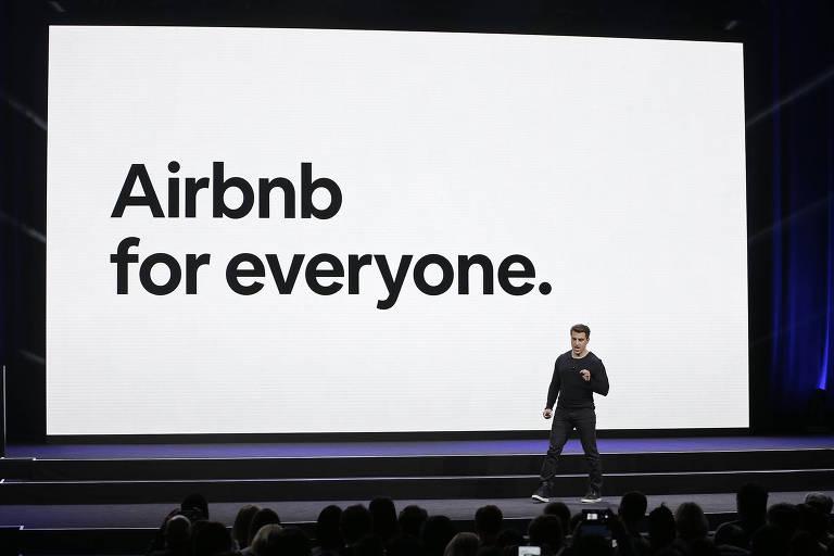 """executivo da airbnb fala diante de uma plateia e, no fundo, uma placa diz """"airbnb for everyone"""""""""""