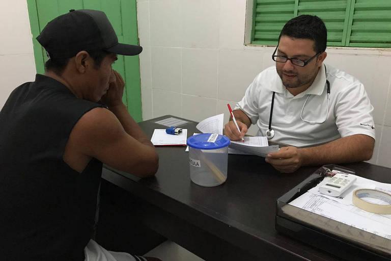 Imagem mostra homem indígena vestindo camiseta preta e usando boné sentado em mesa de frente a médico com roupas brancas, que segura um papel e porta um estetoscópio sobre o pescoço