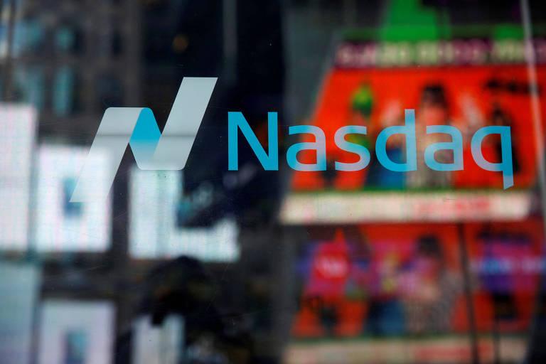 O logo da Nasdaq, Bolsa de valores americana é visto em um vidro que reflete vários monitores da Times Square, em Nova York.