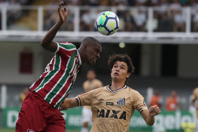 O lateral Dodô (à dir.) disputa a bola em partida contra o Fluminense na Vila Belmiro