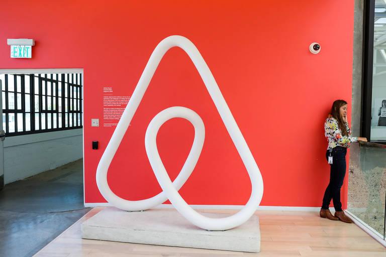 Mulher em frente ao logotipo do Airbnb; empresa poderá abrir capital em 2019