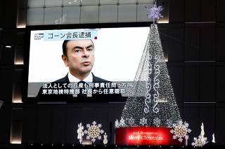 A street monitor showing a news report about arrest of Nissan Chairman Carlos Ghosn is seen next to Christmas illuminations in Tokyo