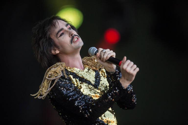 Cantor Johnny Hooker se apresenta no festival Rock in Rio 2017 com roupa preta e detalhes amarelos. Ele segura o microfone e está com a cabeça inclinada para a direita dele