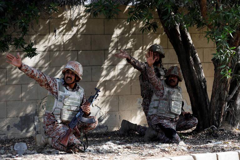 Soldados paquistaneses se protegem em muro em meio a intenso tiroteio com terroristas separatistas que tentaram invadir o Consulado da China em Karachi, no Paquistão