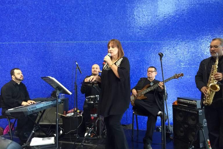 Banda Carisma se apresenta ao vivo, com todos os integrantes vestidos de preto. Um toca teclado, outro, bateria, um está com o baixo, e outro segura um saxofone. A cantora Vera Lúcia está à frente deles, em primeiro plano, com o microfone