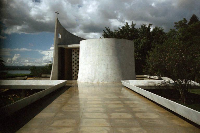 Capela do Palácio da Alvorada; construção fica à esquerda de quem entra na residência oficial do presidente da República; é cilíndrica e branca, pequena e singela vista de fora, ao fim de uma passarela que sai do corpo principal do edifício