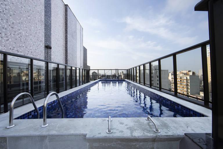Piscina em terraço de edifício em São Paulo. Há grades protetoras transparentes que permitem vista para outros prédios da região