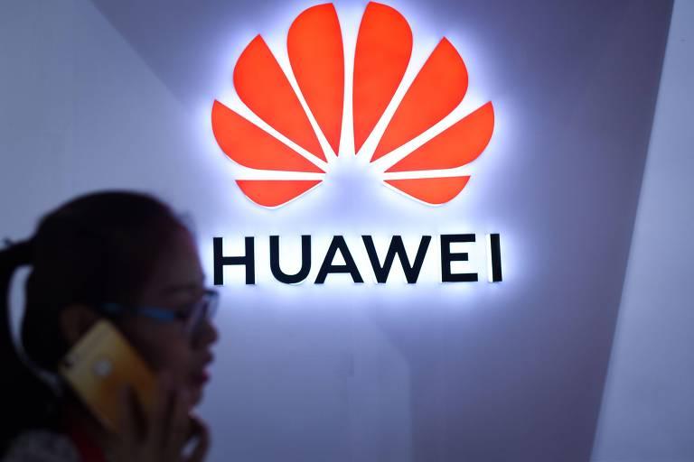 Mulher em frente ao logo da Huawei, em Pequim, na China