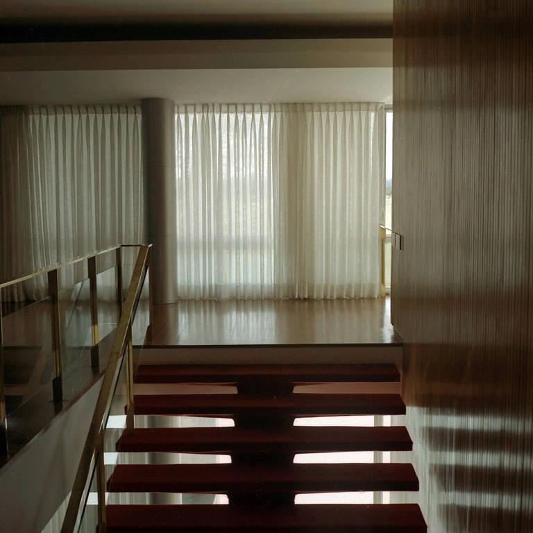 A escadaria que sai do Salão Nobre e leva à ala íntima do palácio; os degraus são forrados de vermelho, os corrimãos são dourados; há uma luz difusa através de cortinas translúcidas