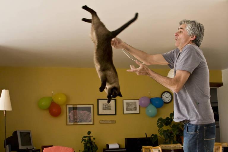 Reinaldo Moraes brinca com gata no seu apartamento de São Paulo.