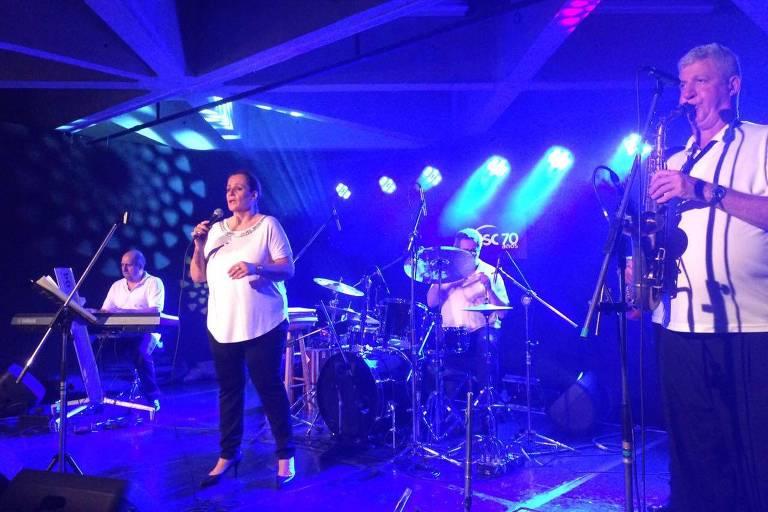 Banda Carisma se apresenta ao vivo, com os integrantes vestidos de branco. Um deles toca teclado, outro, bateria, um segura o saxofone. A cantora Vera Lúcia está em primeiro plano
