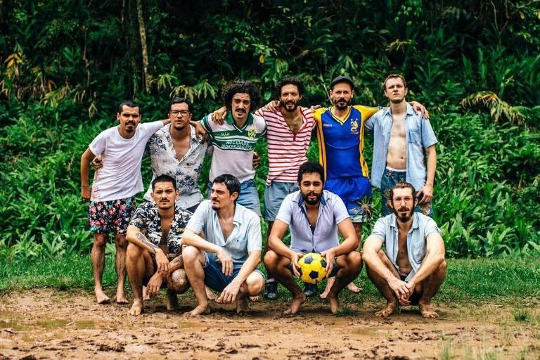dez homens em formação de time de futebol em chão de terra