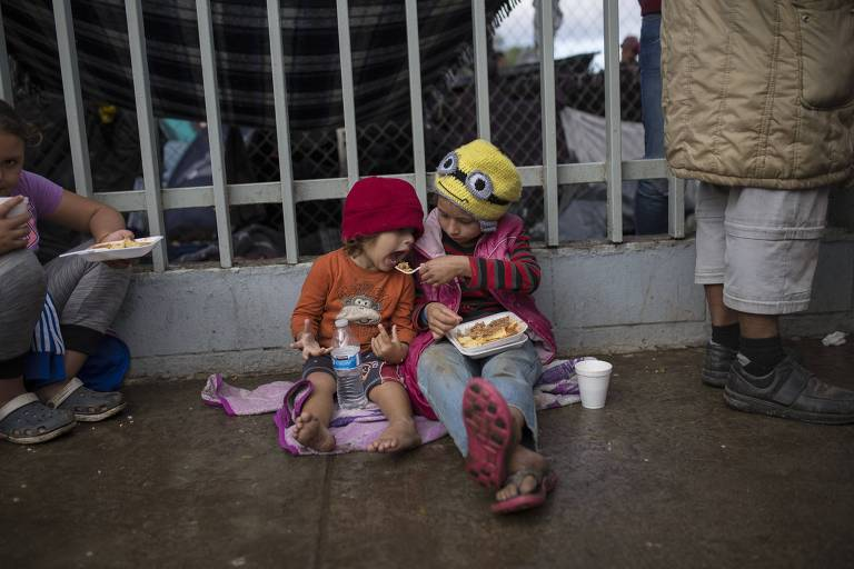 Merary Alejandra alimenta sua irmã de três anos, Britany Sofia, na frente de um abrigo para migrantes em Tijuana