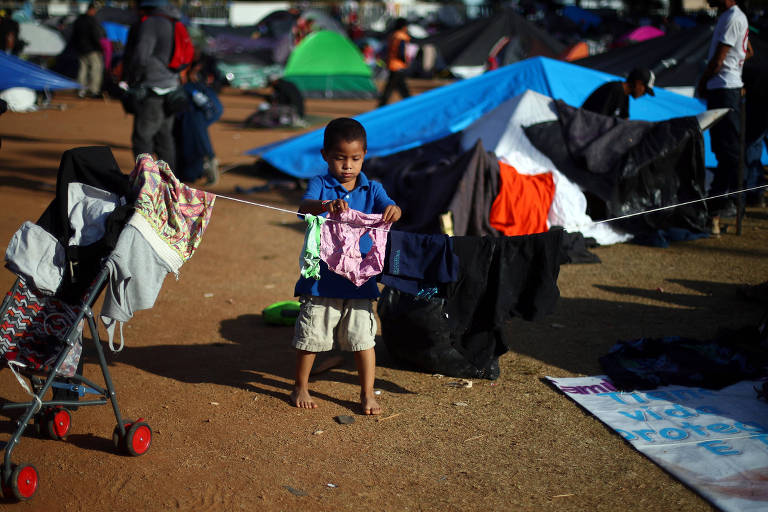 Menino migrante, parte da caravana de milhares de centro-americanos tentando chegar aos EUA, coloca roupa para secar em um abrigo em Tijuana