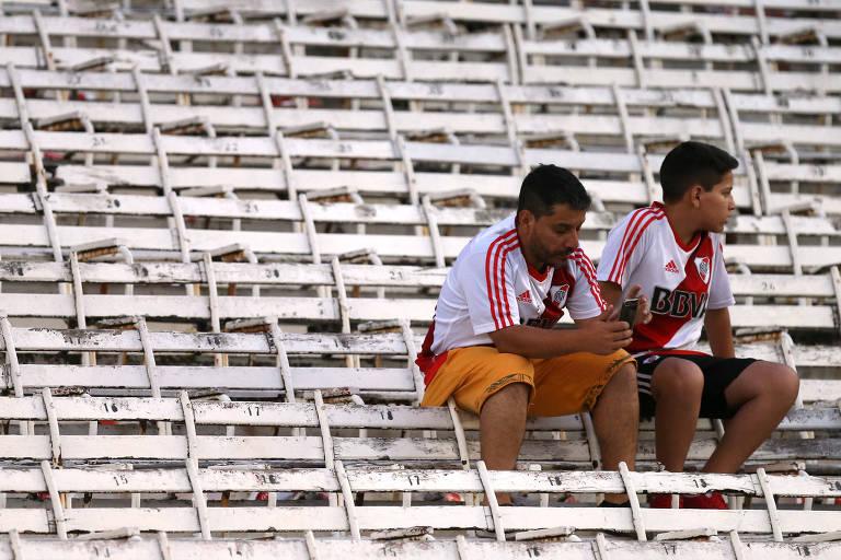 Torcedores sentados nas cadeiras do Monumental após o adiamento da partida