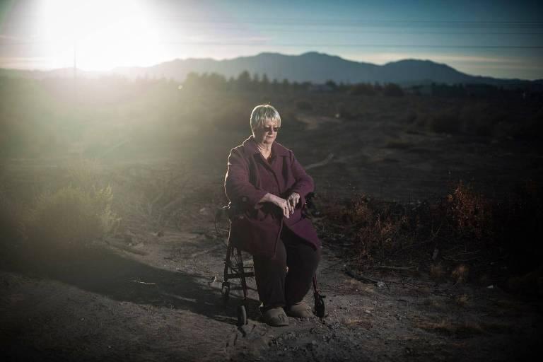 mulher senta em cadeira no meio do deserto