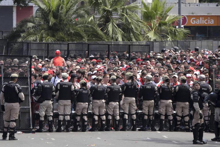 Policiais fazem barreira fora do Monumental de Nuñez antes do anúncio do adiamento da final da Libertadores neste domingo (25)
