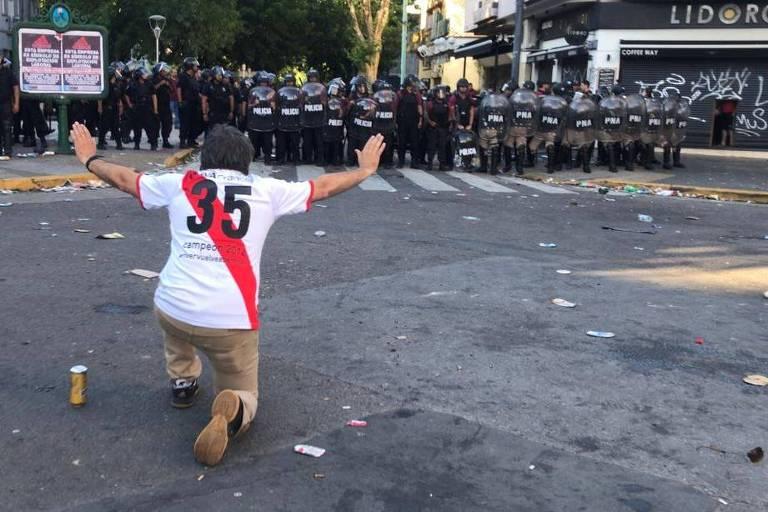Torcedor do River Plate se ajoelha e pede calma diante de policiais após o ataque ao ônibus do Boca Juniors, em Buenos Aires