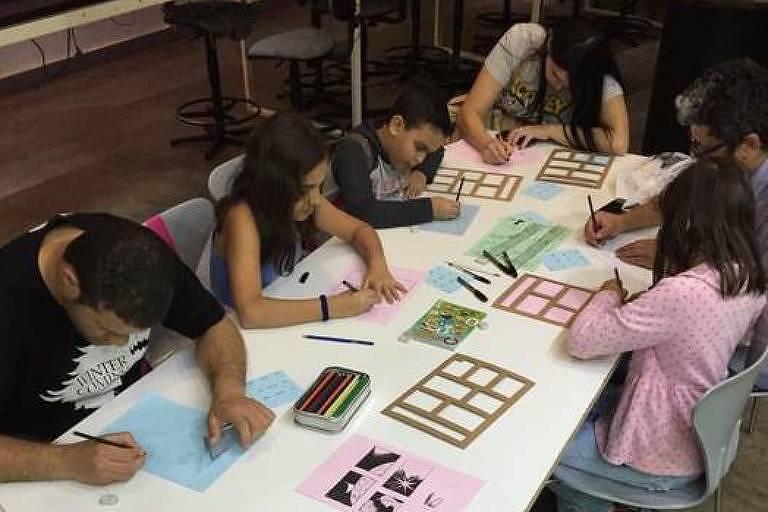 Sentados à mesa, alunos desenham em oficina de criação de páginas em quadrinhos na Fábrica de Cultura