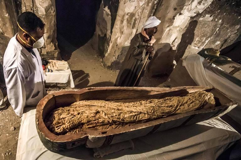 Egípcios ao lado de sarcófago aberto com múmia bem preservada de uma mulher chamada Thuya