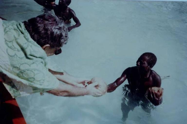 TN Pandit entrega um coco para um membro da tribo sentinela; ele visitou a tribo pela primeira vez em 1973