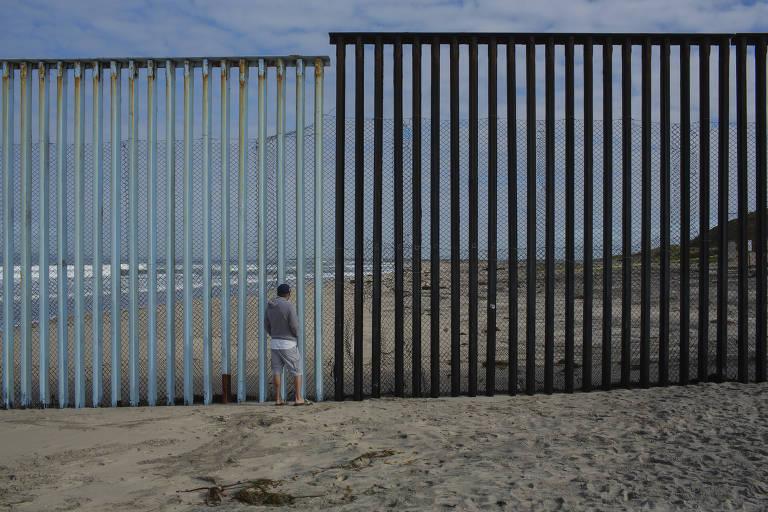 Homem em praia de Tijuana, no México, e o muro que a separa de San Diego (EUA)