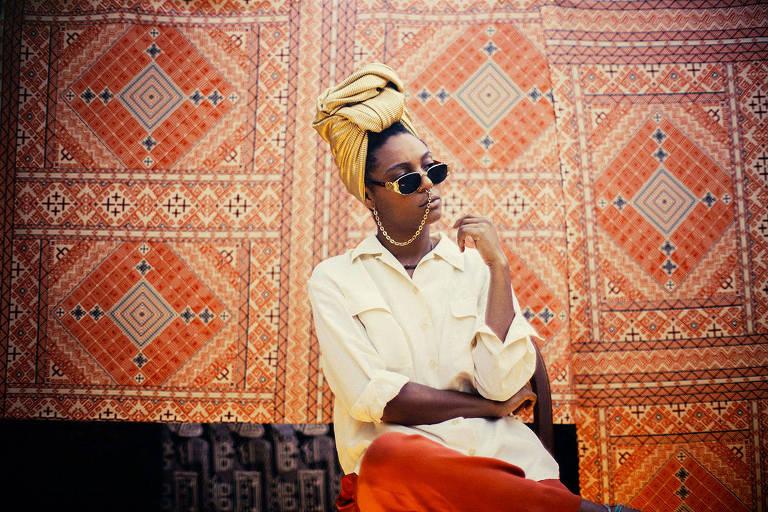 Com turbante cor de abacate na cabeça e de óculos escuros, cantora Bia Ferreira posa sentada em frente a tapetes pendurados