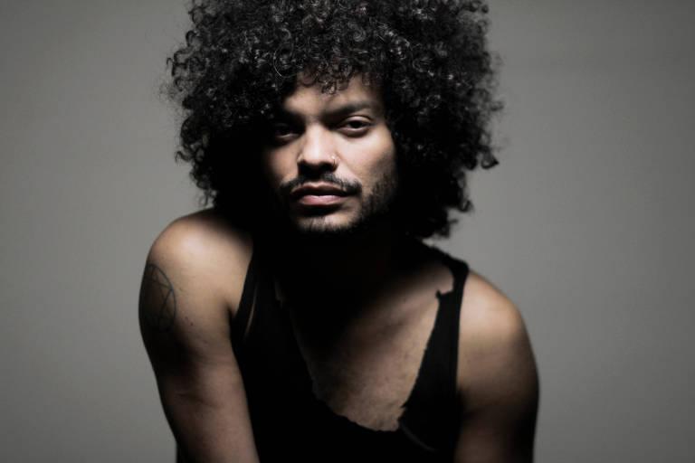 Com cabelão cacheado e vestido com uma regata preta, cantor Diego Moraes posa para foto