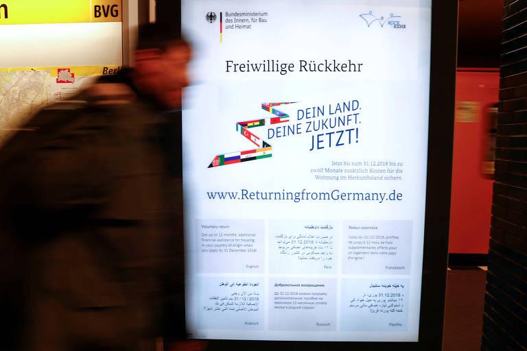 Homem passa diante de anúncio sobre retorno de refugiados a seus países em Berlim